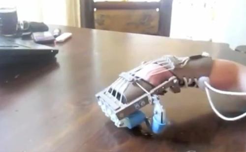 Liam (5) har ingen fingre, men denne håndprotesen lar den vesle gutten plukke opp objekter så små som kronestykker. Foto: Skjermdump / YouTube